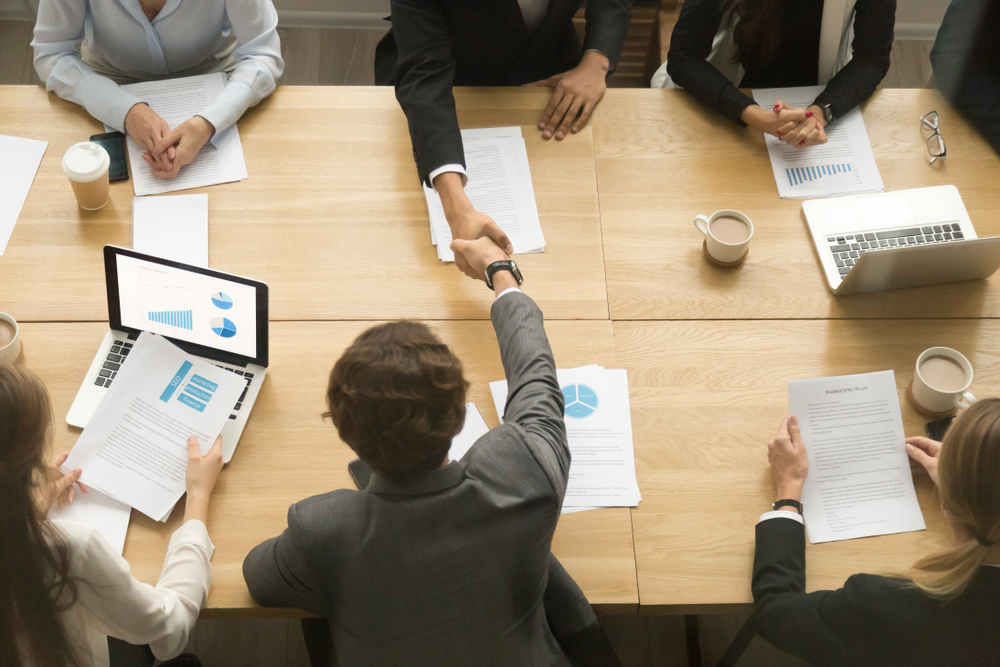 Businessmen shaking hands sitting at conference table
