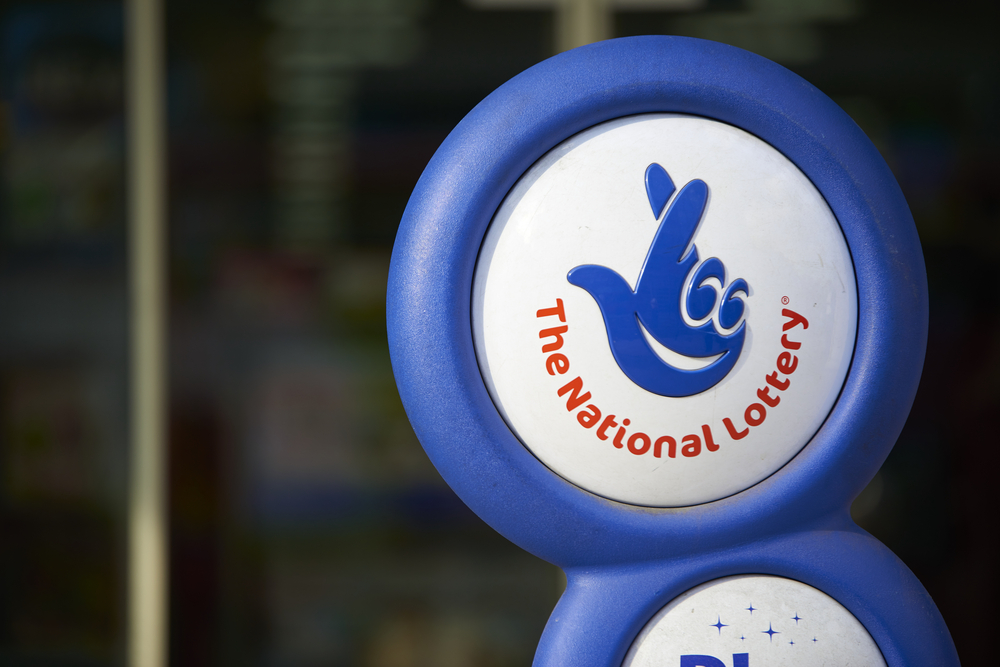 Close up of blue National lottery sign in front of shop