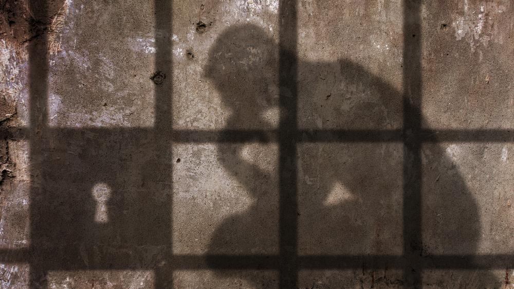 thinking man behind bars