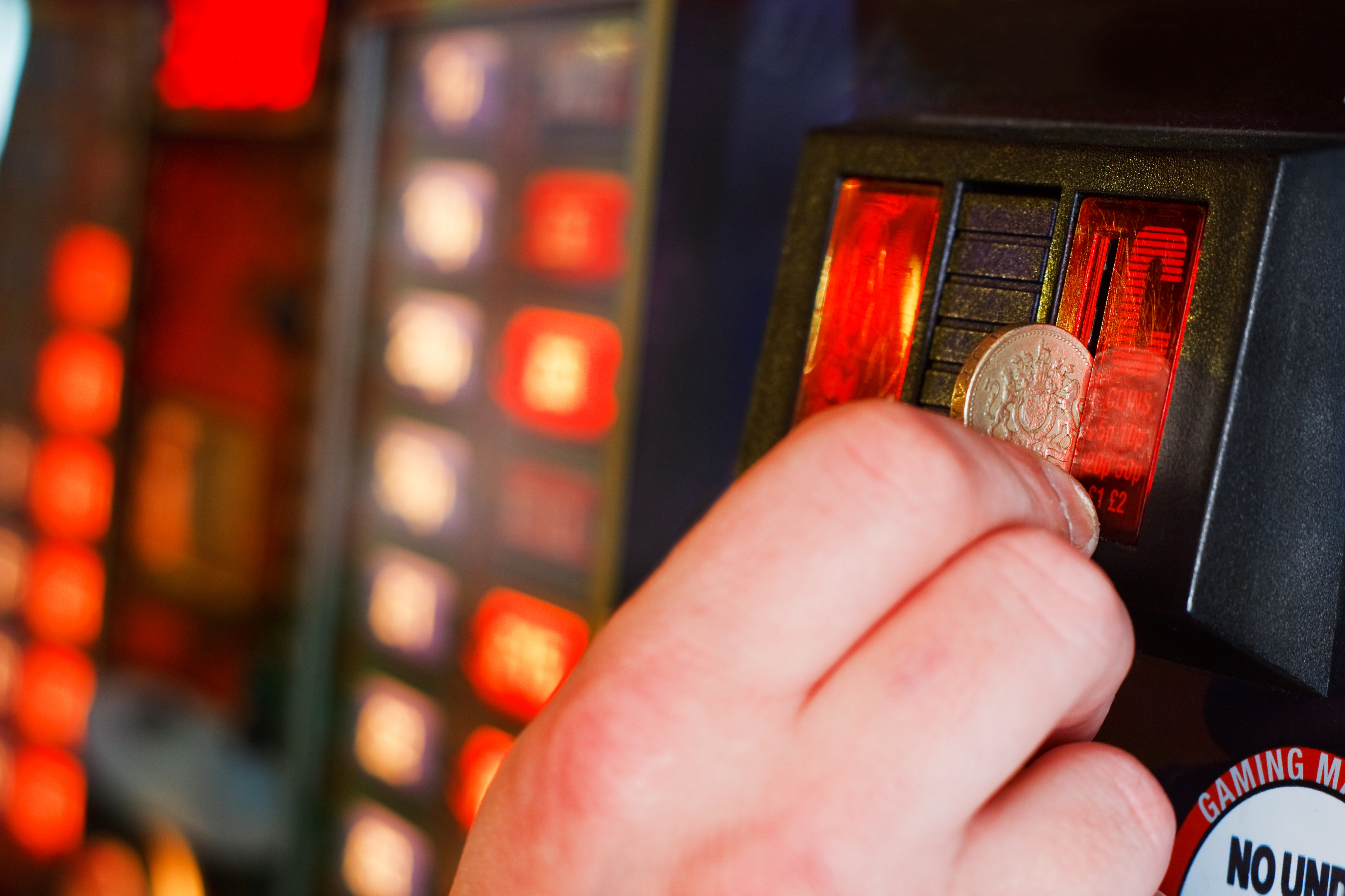 hand putting pound coin into fruit machine