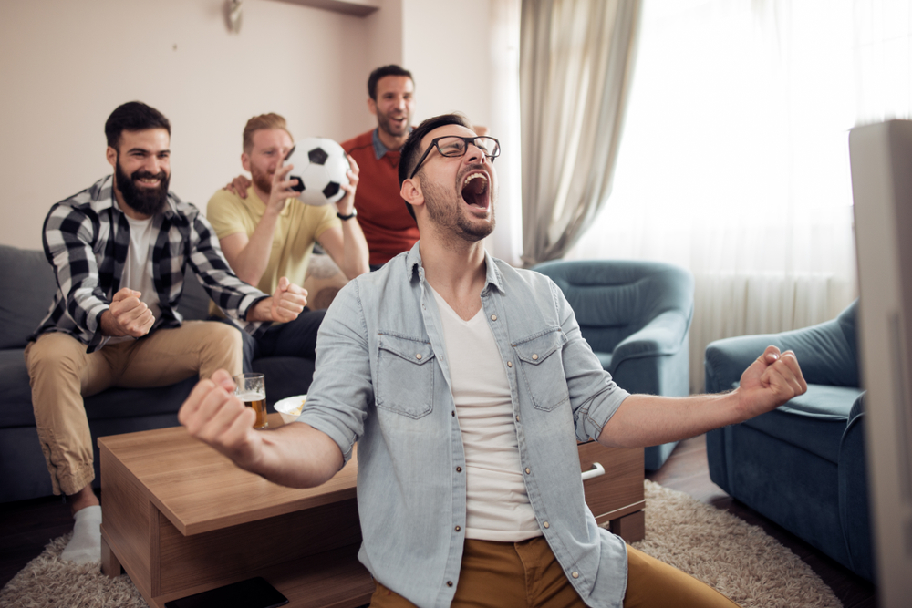 football fans watching soccer on tv and celebrating victory