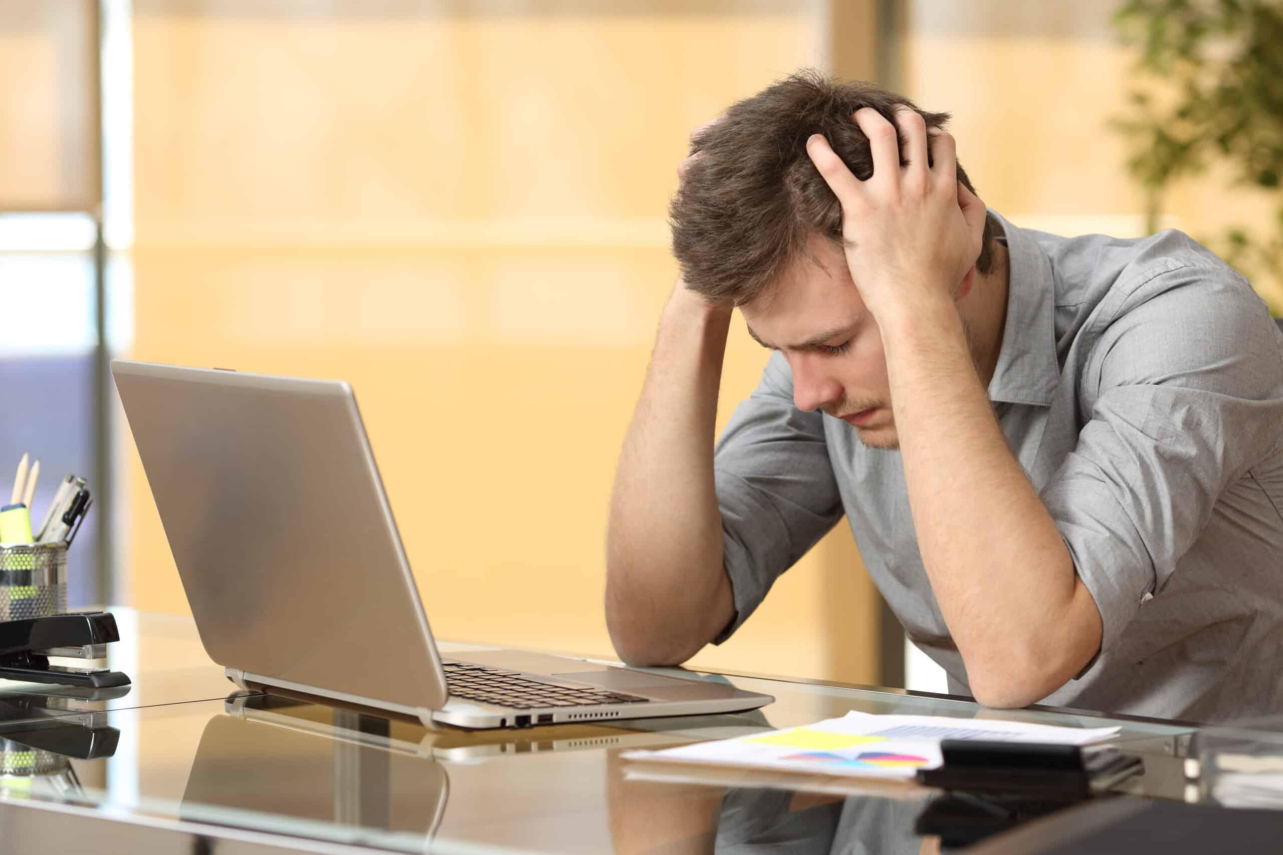 worried man sitting at laptop
