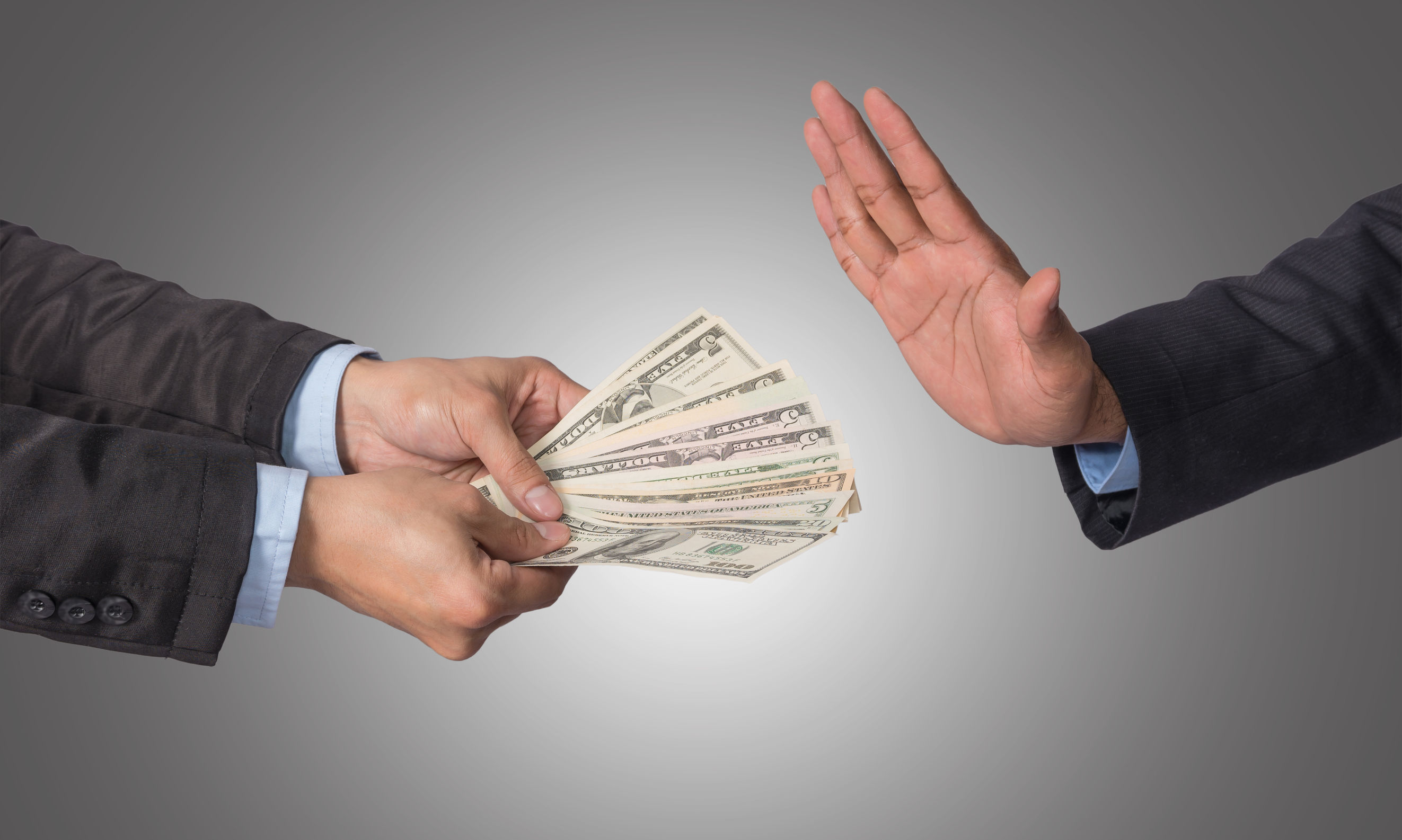 Businessman refusing the money offered by businessman on white b