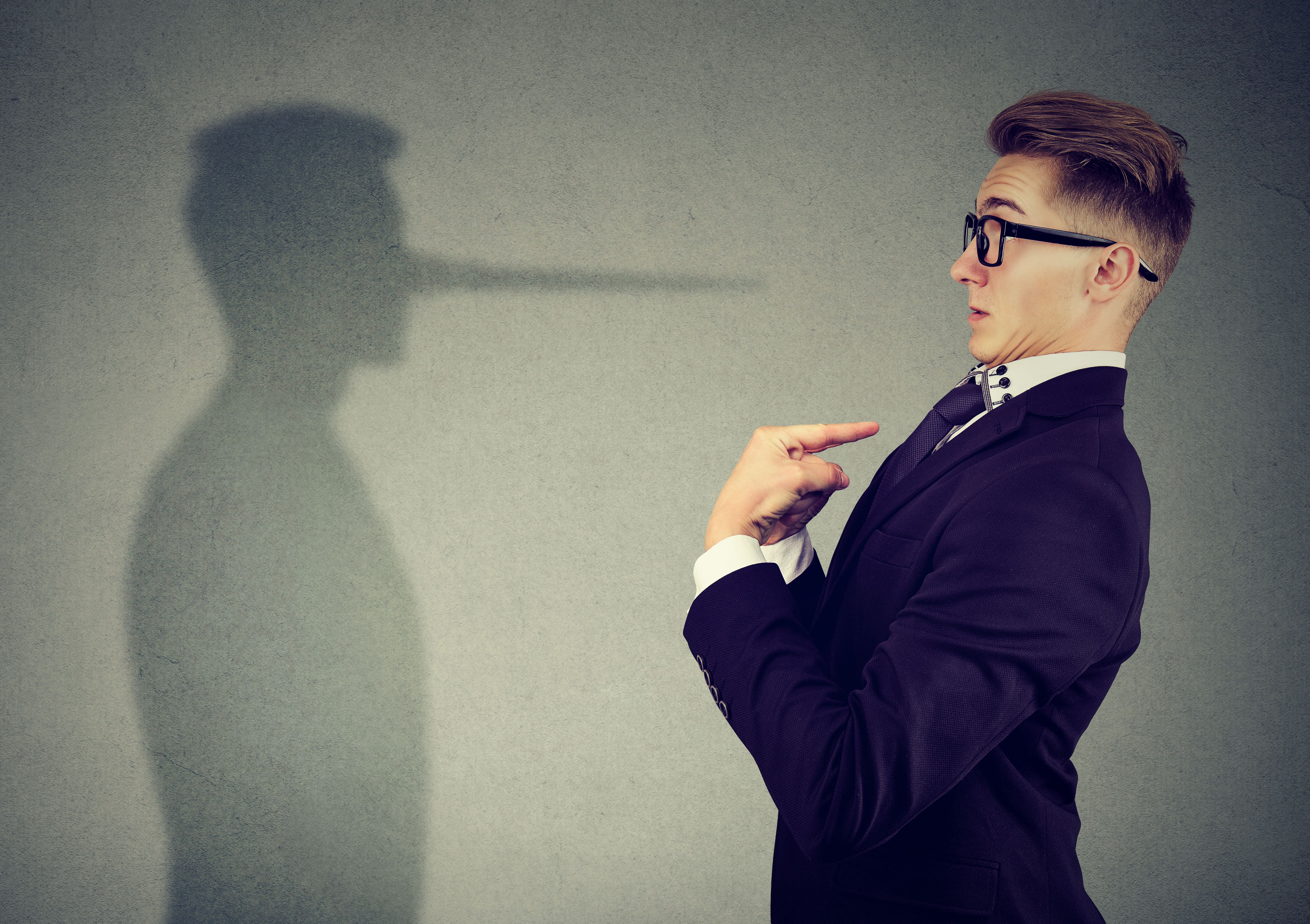 Side view of man in suit pointing at himself looking at shadow with long nose of a liar