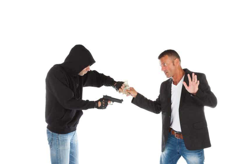 Robber with gun grabbing money from victim