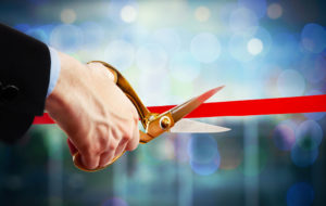 businessman cutting red ribbon