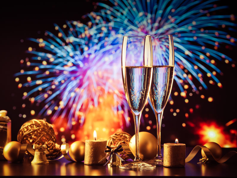 two champagne glasses against holiday lights and fireworks - new
