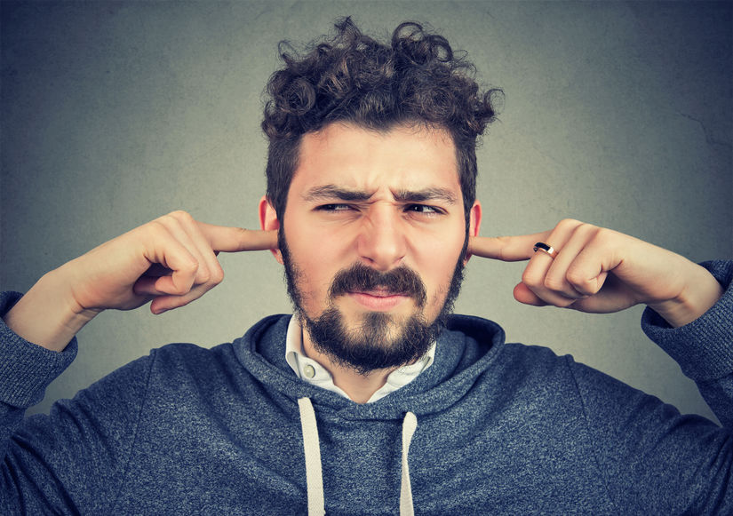 displeased man plugging ears annoyed by loud noise